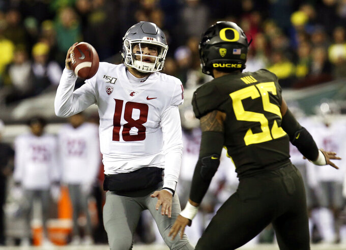 Washington State's Anthony Gordon, left, scrambles under pressure from Oregon's Sampson Niu during the second quarter of an NCAA college football game Saturday, Oct. 26, 2019, in Eugene, Ore. (AP Photo/Chris Pietsch)