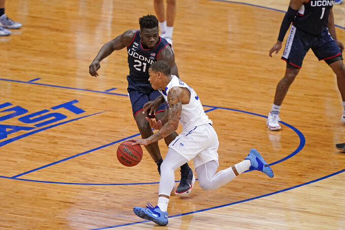Seton Hall guard Shavar Reynolds (33) drives around Connecticut forward Adama Sanogo (21) during the second half of an NCAA college basketball game Wednesday, March 3, 2021, in Newark, N.J. (AP Photo/Kathy Willens)