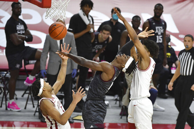 Texas A&M forward Emanuel Miller (5) is fouled as he tries to get past Arkansas defenders Moses Moody (5) and JD Notae (1) during the second half of an NCAA college basketball game in Fayetteville, Ark., Saturday, March 6, 2021. (AP Photo/Michael Woods)