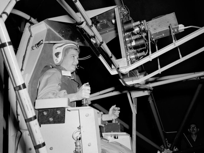 In this 1960 photo made available by NASA, Jerrie Cobb prepares to operate the Multi-Axis Space Test Inertia Facility (MASTIF) at the Lewis Research Center in Ohio.  The three-axis rig was developed to train Project Mercury pilots in bringing a spinning spacecraft under control. The two controllers in Cobb's hands activated small nitrogen gas thrusters that were used to bring the MASTIF under control. She was one of several female pilots who underwent the skill and endurance testing that paralleled that of the Project Mercury astronauts. In 1961 Jerrie Cobb was the first female to pass all three phases of the Mercury Astronaut Program. NASA rules, however, stipulated that only military test pilots could become astronauts and there were no female military test pilots. Cobb, NASA's first female astronaut candidate, died in Florida at the age of 88 on March 18, 2019. (NASA via AP)