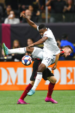 New England Revolution forward DeJuan Jones, left, and Atlanta United defender Julian Gressel, right, vie for the ball during the first half of round one of an MLS Cup playoff soccer game Saturday, Oct. 19, 2019, in Atlanta. (AP Photo/John Amis)