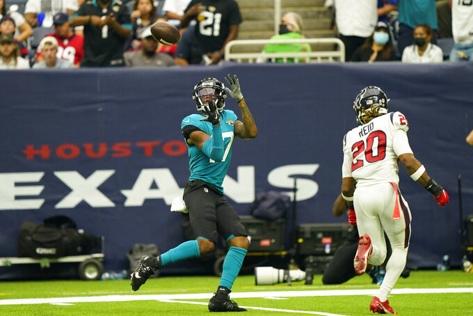 Jacksonville Jaguars wide receiver DJ Chark Jr. (17) catches a pass for a touchdown as Jacksonville Jaguars safety Daniel Thomas (20) defends during the second half of an NFL football game Sunday, Sept. 12, 2021, in Houston. (AP Photo/Eric Christian Smith)