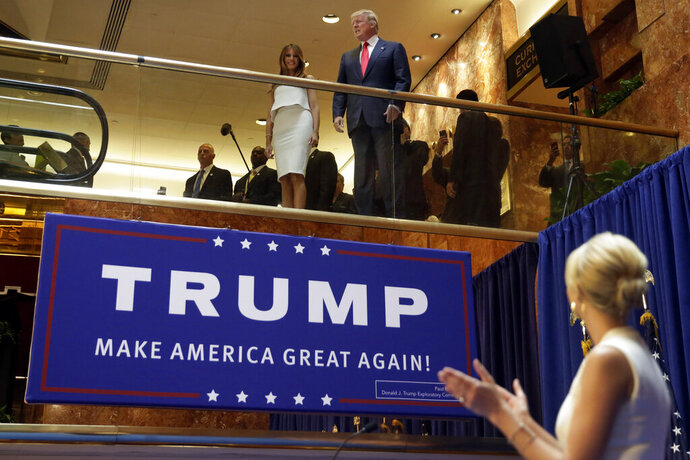 FILE - In this Sunday, June 16, 2015, file photo, Donald Trump, accompanied by his wife Melania Trump, is applauded by his daughter Ivanka Trump, right as he's introduced before his announcement that he will run for president in the lobby of Trump Tower in New York. It was the escalator ride that would change history. Four years ago on Sunday, Donald Trump descended through the marble and brass atrium of Trump Tower to announce his candidacy for president. It was the first step on a journey few believed would take him all the way to the White House. (AP Photo/Richard Drew, File)