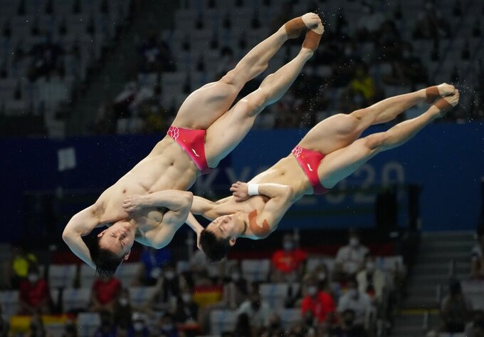 Wang Zongyuan and Xie Siyi of China compete during the men's Synchronized 3m Springboard Final at the Tokyo Aquatics Centre at the 2020 Summer Olympics, Wednesday, July 28, 2021, in Tokyo, Japan. (AP Photo/Dmitri Lovetsky)