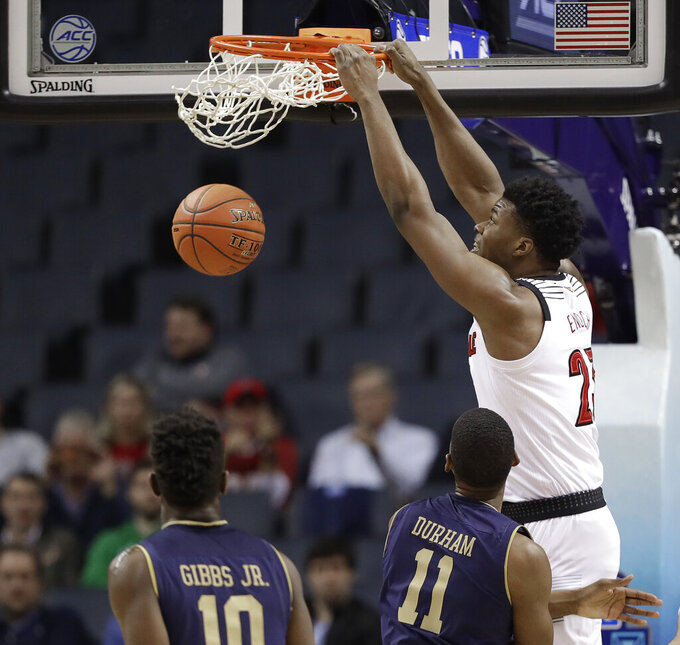Louisville's Steven Enoch (23) dunks past Notre Dame's Juwan Durham (11) and TJ Gibbs (10) during the first half of an NCAA college basketball game in the Atlantic Coast Conference tournament in Charlotte, N.C., Wednesday, March 13, 2019. (AP Photo/Chuck Burton)