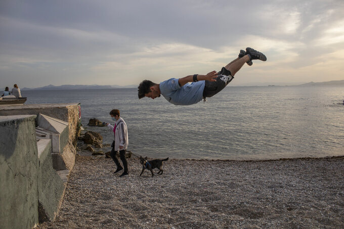 25 year-old Jimmakos Scotis makes a backflip as a woman wearing a protective face mask walks with her dog at the seaside of Alimos, suburb of Athens, on Tuesday, May 4, 2021. Greece began easing coronavirus-related restrictions with a view to opening to the vital tourism industry in the summer. (AP Photo/Petros Giannakouris)