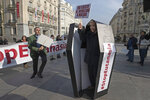 A protester from the pro-life group Derecho a Vivir stands in a mock coffin outside the Spanish parliament in Madrid, Spain, Tuesday, Feb. 11, 2020. Spain's new parliament is expected to accept in its first legislative session a majority vote the debate on a law that decriminalizes and regulates euthanasia. Banner reads ;'The right to kill does not exist'. (AP Photo/Paul White)