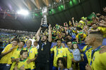 Brazil's goalkeeper Alisson lifts up his team's trophy after they won the final soccer match of the Copa America against Peru at Maracana stadium in Rio de Janeiro, Brazil, Sunday, July 7, 2019. Brazil won 3-1. (AP Photo/Leo Correa)