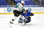 St. Louis Blues' David Perron, right, slips as San Jose Sharks' Brent Burns defends during overtime of an NHL hockey game Wednesday, Jan. 20, 2021, in St. Louis. (AP Photo/Jeff Roberson)