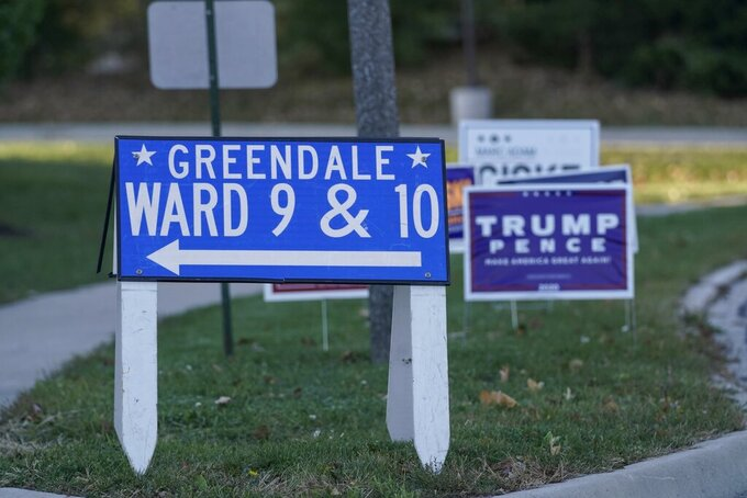 Political signs are seen outside the Greendale Police station and polling locxation Tuesday, Nov. 3, 2020, in Greenfield, Wis. (AP Photo/Morry Gash)