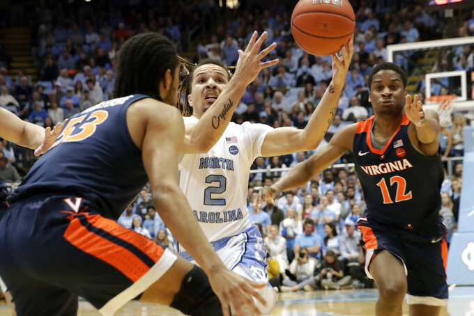 North Carolina's Cole Anthony (2) drives against Virginia's Tomas Woldetensae (53) and Chase Coleman (12) during the first half of an NCAA college basketball game at the Dean Smith Center in Chapel Hill, N.C., Saturday, Feb. 15, 2020. (AP Photo/Chris Seward)