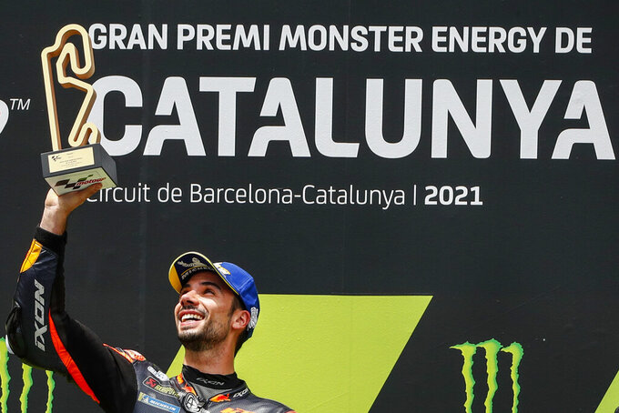 Portugal's Miguel Oliveira of KTM holds the trophy from the podium after winning the Catalunya Motorcycle Grand Prix at the Barcelona Catalunya racetrack in Montmelo, near Barcelona, Spain, Sunday, June 6, 2021. (AP Photo/Joan Monfort)