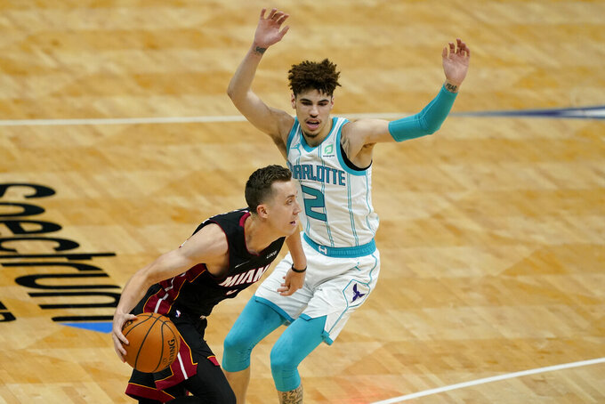 Miami Heat guard Goran Dragic drives to the basket past Charlotte Hornets guard LaMelo Ball during the first half of an NBA basketball game on Sunday, May 2, 2021, in Charlotte, N.C. (AP Photo/Chris Carlson)