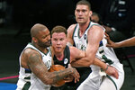 Milwaukee Bucks center Brook Lopez, right, holds onto Brooklyn Nets forward Blake Griffin to keep him from Bucks forward P.J. Tucker, left, who tries to hold onto the ball during the second half of Game 2 of an NBA basketball second-round playoff series, Monday, June 7, 2021, in New York. (AP Photo/Kathy Willens)
