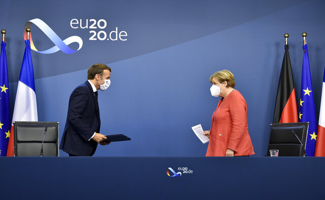 German Chancellor Angela Merkel, right, and French President Emmanuel Macron prepare to address a media conference at the end of an EU summit in Brussels, Tuesday, July 21, 2020. Weary European Union leaders finally clinched an unprecedented budget and coronavirus recovery fund early Tuesday, finding unity after four days and as many nights of fighting and wrangling over money and power in one of their longest summits ever. (John Thys, Pool Photo via AP)