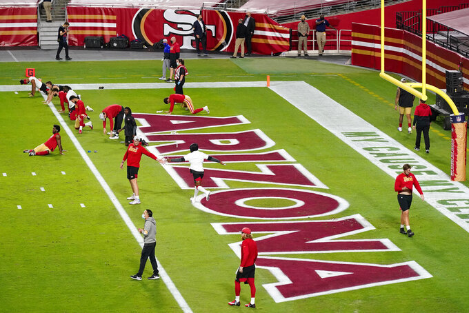 San Francisco 49ers players stretch prior to an NFL football game against the Buffalo Bills, Monday, Dec. 7, 2020, in Glendale, Ariz. (AP Photo/Ross D. Franklin)
