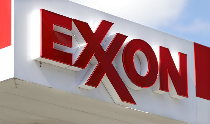 FILE- This April 25, 2017, file photo, shows an Exxon service station sign in Nashville, Tenn.  Exxon Mobil reported on Friday, Oct. 30, 2020, lost $680 million in the third quarter as the global pandemic curtailed travel throughout the world, diminishing the need for fuel. Revenue tumbled to $46.2 billion, down from $65.05 billion during the same quarter last year.(AP Photo/Mark Humphrey, File)