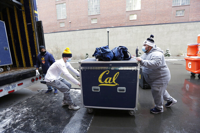 California student managers Marino Baca, right, and Tomy Wymore, center, load equipment onto the team's truck as equipment truck driver Hector Cardosa looks on outside Martin Stadium at Martin Stadium after the NCAA college football game between Washington State and California was canceled because of a case of COVID-19 on the Cal team, Saturday, Dec. 12, 2020, in Pullman, Wash. (AP Photo/Young Kwak)