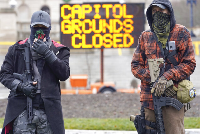 Members of the Boogaloo Boys, holding semi-automatic weapons stand outside at the Capitol building in Frankfort, Ky., Wednesday, Jan 17, 2021. The Capitol, the Capitol complex, and surrounding grounds have been closed. (AP Photo/Bryan Woolston)