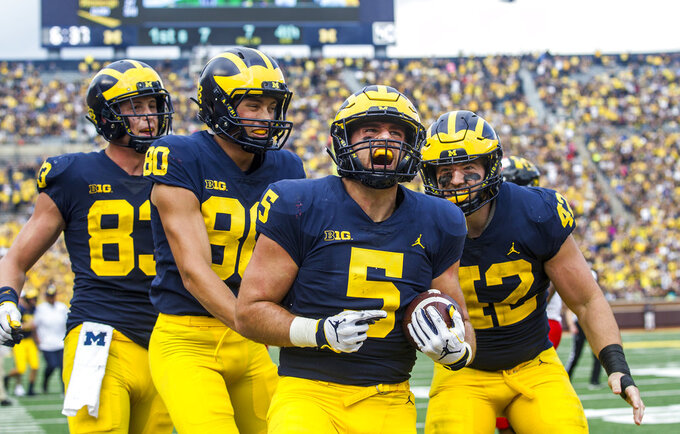 Michigan fullback Jared Wangler (5) celebrates his seven-yard touchdown reception with tight end Zach Gentry (83), wide receiver Oliver Martin (80), and fullback Ben Mason (42), in the fourth quarter of an NCAA college football game against Maryland in Ann Arbor, Mich., Saturday, Oct. 6, 2018. Michigan won 42-21. (AP Photo/Tony Ding)