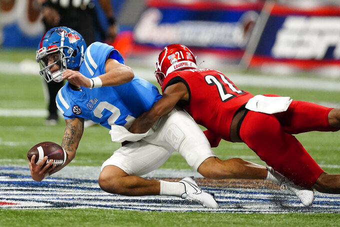 Mississippi quarterback Matt Corral (2) is tackled by Louisville defensive back Greedy Vance (21) during the first half of an NCAA college football game Monday, Sept. 6, 2021, in Atlanta. (AP Photo/John Bazemore)