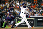 Houston Astros designated hitter Yordan Alvarez (44) hits a two run home run in front of Cleveland Indians catcher Roberto Perez, center, and umpire Edwin Moscoso, left, during the fifth inning of a baseball game Monday, July 19, 2021, in Houston. (AP Photo/Michael Wyke)