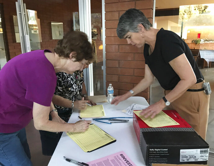 Melanie Beikman, right, Thousands of teachers in Arizona, gathers signatures Thursday, May 10, 2018 in Phoenix for a ballot initiate to raise the income tax on wealthy earners to fund public education Oklahoma and West Virginia are turning their attention to political activities after organizing in massive statewide teacher movements. (AP Photo/Melissa Daniels)