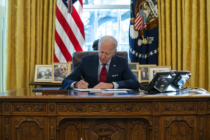 FILE - In this Jan. 28, 2021, file photo President Joe Biden signs a series of executive orders on health care, in the Oval Office of the White House in Washington. (AP Photo/Evan Vucci, File)
