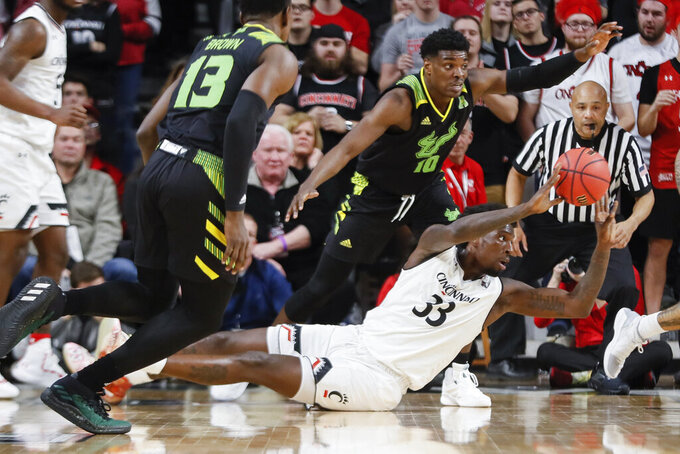Cincinnati's Nysier Brooks (33) passes after retrieving a loose ball against South Florida's Alexis Yetna (10) in the first half of an NCAA college basketball game, Tuesday, Jan. 15, 2019, in Cincinnati. (AP Photo/John Minchillo)