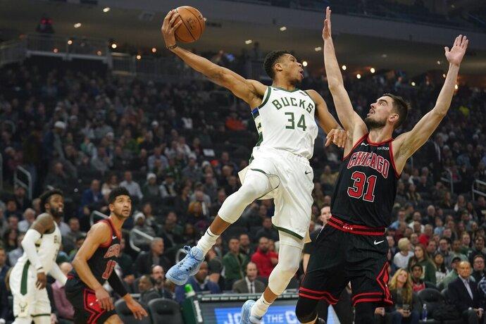 Milwaukee Bucks' Giannis Antetokounmpo looks to pass around Chicago Bulls' Tomas Satoransky during the first half of an NBA basketball game Thursday, Nov. 14, 2019, in Milwaukee. (AP Photo/Morry Gash)
