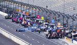 Drivers stop in the pits for tire changes during qualifying for an IndyCar auto race at Indianapolis Motor Speedway, Friday, Aug. 13, 2021, in Indianapolis. (AP Photo/Doug McSchooler)