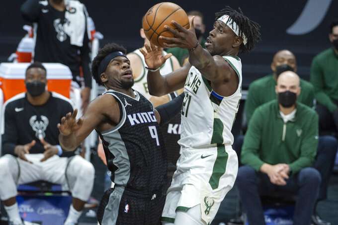 Sacramento Kings guard Terrence Davis (9) defends against Milwaukee Bucks guard Jrue Holiday (21) during the second half of an NBA basketball game in Sacramento, Calif., Saturday, April 3, 2021. The Bucks won 129-128. (AP Photo/Randall Benton)