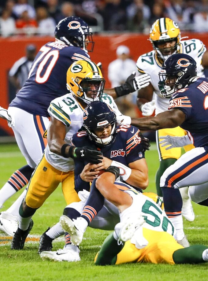 Chicago Bears' Mitchell Trubisky is sacked by Green Bay Packers' Blake Martinez and Adrian Amos during the first half of an NFL football game Thursday, Sept. 5, 2019, in Chicago. (AP Photo/Charles Rex Arbogast)