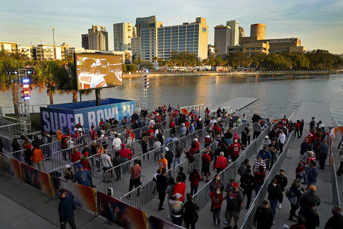 People watch a video at the NFL Experience Thursday, Feb. 4, 2021, in Tampa, Fla. The city is hosting Sunday's Super Bowl football game between the Tampa Bay Buccaneers and the Kansas City Chiefs. (AP Photo/Charlie Riedel)