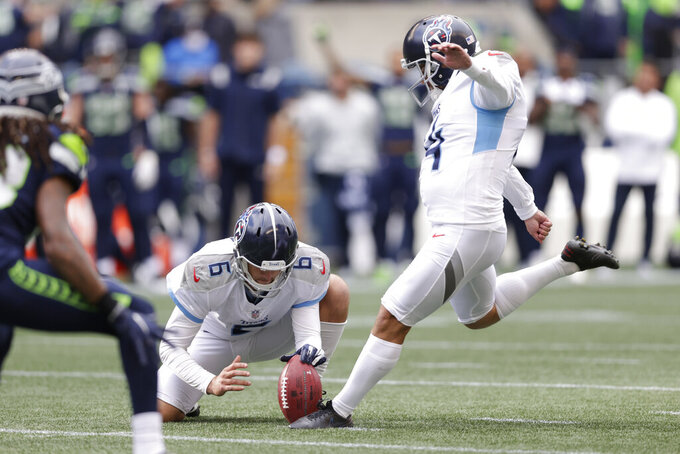 Tennessee Titans kicker Randy Bullock, right, kicks a field goal in overtime as Brett Kern holds to give the Titans a 33-30 win over the Seattle Seahawks in an NFL football game, Sunday, Sept. 19, 2021, in Seattle. (AP Photo/John Froschauer)