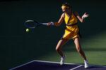 Victoria Azarenka, of Belarus, returns a shot to Jessica Pegula at the BNP Paribas Open tennis tournament Wednesday, Oct. 13, 2021, in Indian Wells, Calif. (AP Photo/Mark J. Terrill)