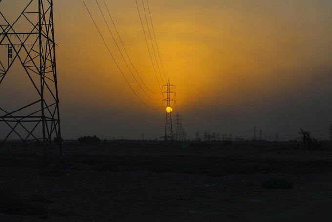 The sun sets behind the transmission lines of electric power from Iran to Iraq in Basra, Iraq, Tuesday, July 29, 2021. In Iraq, electricity is a potent symbol of endemic corruption, rooted in the country's sectarian power-sharing system. This contributes to chronic electrical outages of up to 14 hours a day in a major oil-producing nation with plentiful energy resources. (AP Photo/Nabil al-Jurani)