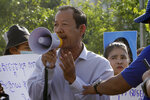 FILE - In this July 29, 2020, file photo, Rong Chhun, president of the Cambodian Confederation of Unions, uses a megaphone during a protest near the prime minister's residence in Phnom Penh, Cambodia. Rong Chhun was sentenced Wednesday, Aug. 18, 2021 to two years in prison for inciting social unrest with sensitive comments about the country's border. (AP Photo/Heng Sinith, File)