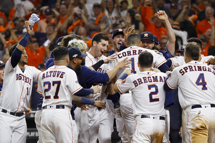 Houston Astros' Carlos Correa celebrates with teammates after his walk-off home run against the New York Yankees during the 11th inning in Game 2 of baseball's American League Championship Series Sunday, Oct. 13, 2019, in Houston. (AP Photo/Eric Gay)