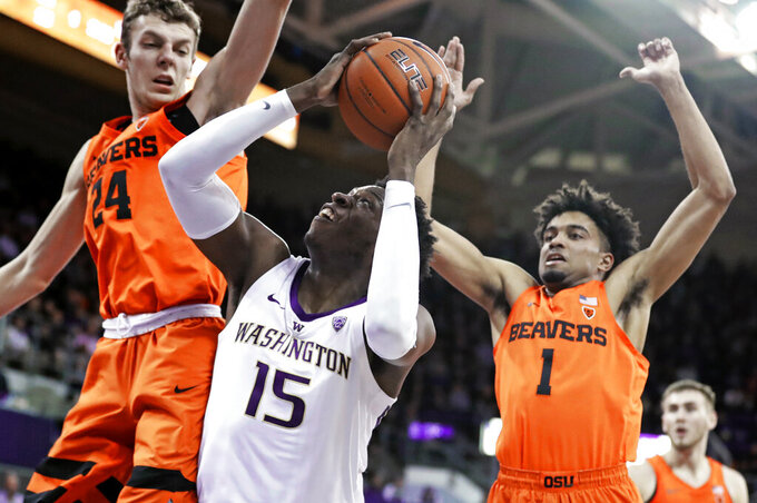 Washington forward Noah Dickerson (15) tries to get a shot off as Oregon State's Kylor Kelley, left, and Stephen Thompson Jr., right, defend during the first half of an NCAA college basketball game Wednesday, March 6, 2019, in Seattle. (AP Photo/Ted S. Warren)