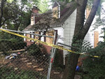 In this Aug. 18, 2018, photo, police tape surrounds the house where Askia Khafra died in a fire while digging underground tunnels for a secretive campaign to build a nuclear bunker in Bethesda, Md. Daniel Beckwitt, a stock trader who lived alone in the house, is charged with second-degree murder and involuntary manslaughter in the Sept. 10, 2017, death of Askia Khafra. (AP Photo/Michael Kunzelman)