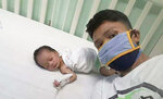 In this photo provided by Ronnel Manjares, he takes a selfie with his son Kobe at a hospital in metropolitan Manila, Philippines, Saturday April 18, 2020. Manjares' 16-day-old son Kobe was heralded as the country's youngest COVID-19 survivor. But the relief and joy proved didn't last. Three days later, Kobe died on June 4 from complications of Hirschsprung disease, a rare birth defect. (Ronnel Manjares via AP) (Ronnel Manjares via AP)
