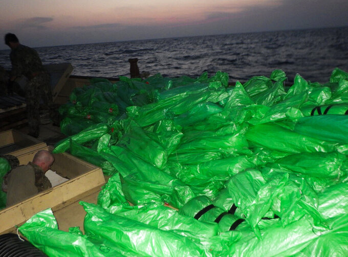 Plastic-wrapped weapons are seen on the deck of a stateless dhow that the U.S. Navy said carried a hidden arms shipment in the Arabian Sea on Friday, May 7, 2021. The U.S. Navy announced Sunday it seized the arms shipment hidden aboard the vessel in the Arabian Sea, the latest-such interdiction by sailors amid the long-running war in Yemen. (U.S. Navy via AP)