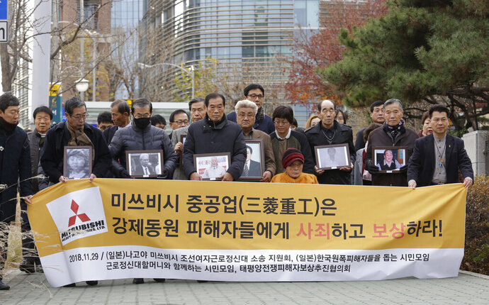 FILE - In this Nov. 29, 2018, file photo, victims of Japan's forced labor and their family members arrive at the Supreme Court in Seoul, South Korea. Colonial-era Korean laborers on Tuesday, July 16, 2019, are seeking a court's approval for the sales of local assets of their former Japanese employer after it refused to comply with a court order to compensate them for forced labor decades ago. The sign reads