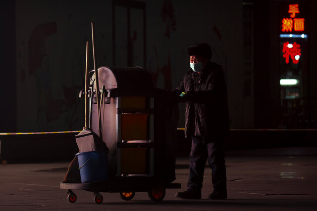 A maintenance worker wearing a face mask to protect against the spread of the coronavirus walks outside of an office complex in Beijing, Wednesday, Jan. 13, 2021. China is concentrating its pandemic prevention efforts in the rural areas as officials urge people to not travel home for the annual Lunar New Year festival, as the country combats its most serious latest outbreak of COVID-19 since the pandemic originally broke out in Wuhan a year ago. (AP Photo/Mark Schiefelbein)