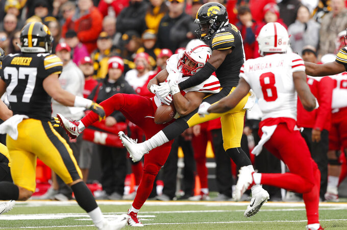 Iowa defensive back Michael Ojemudia (11) breaks up a pass intended for Nebraska running back Devine Ozigbo, center, during the first half of an NCAA college football game, Friday, Nov. 23, 2018, in Iowa City, Iowa. (AP Photo/Charlie Neibergall)