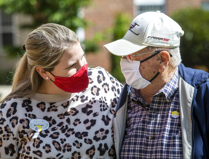 In this Tuesday, May 12, 2020 photo, Marian Lee and Roland Jones talk in the courtyard at Abbotswood at Irving Park in Greensboro, N.. (Woody Marshall/News & Record via AP)