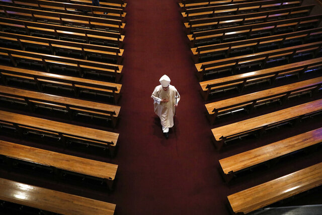 Bishop William Joensen proceeds down the main aisle at the conclusion of Holy Thursday Mass in a near empty St. Ambrose Cathedral, Thursday, April 9, 2020, in Des Moines, Iowa. COVID-19 causes mild or moderate symptoms for most people, but for some, especially older adults and people with existing health problems, it can cause more severe illness or death. (AP Photo/Charlie Neibergall)