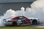 A.J. Allemdinger does a burnout after winning the NASCAR Xfinity Cup Series auto race at Michigan International Speedway, Saturday, Aug. 21, 2021, in Brooklyn, Mich. (AP Photo/Carlos Osorio)