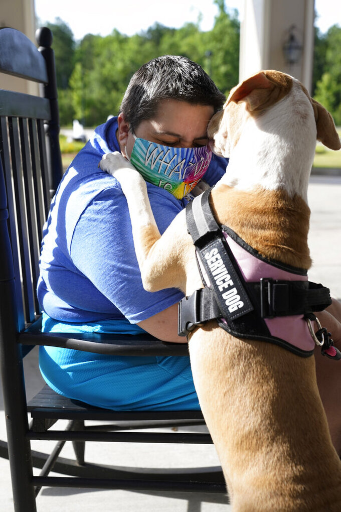 Katrina Folks hugs her service dog, Princess, and speaks about her efforts to find work since losing her job in September because of the coronavirus pandemic, Friday, May 28, 2021, in Hattiesburg, Miss. Folks, the mother of an 11-year old son, used to do data entry at a law firm, but she has health issues that require her to work from home. Mississippi Gov. Tate Reeves announced May 10 that the state will opt out of the $300-a-week federal supplement for people who lost their jobs during the COVID-19 pandemic, as well as other programs that offered extended support for the unemployed, actions, directly affecting Folks. (AP Photo/Rogelio V. Solis)
